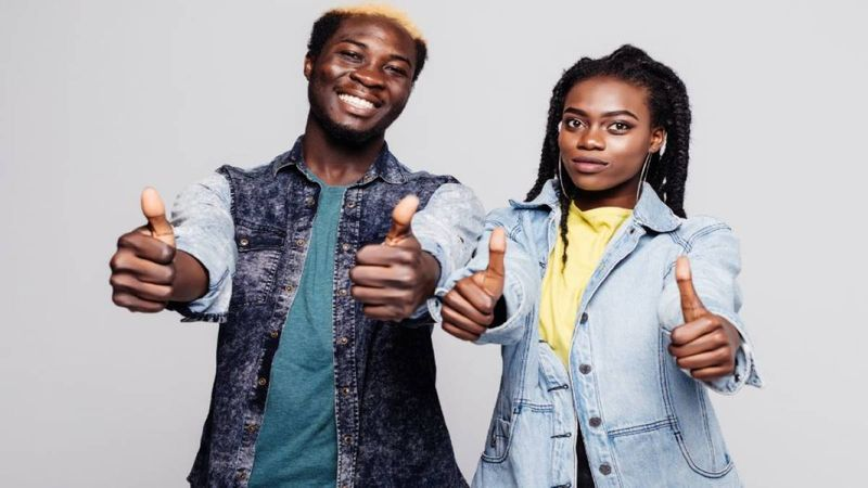 African man and woman with thumbs up