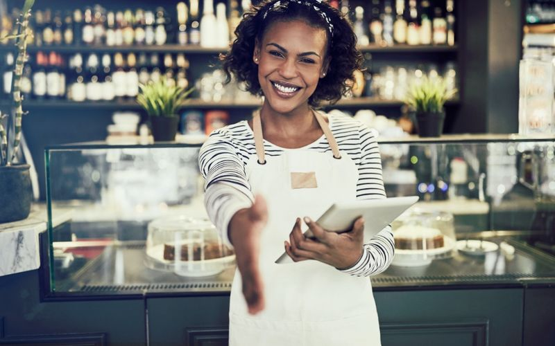 Friendly business-woman welcoming new employee