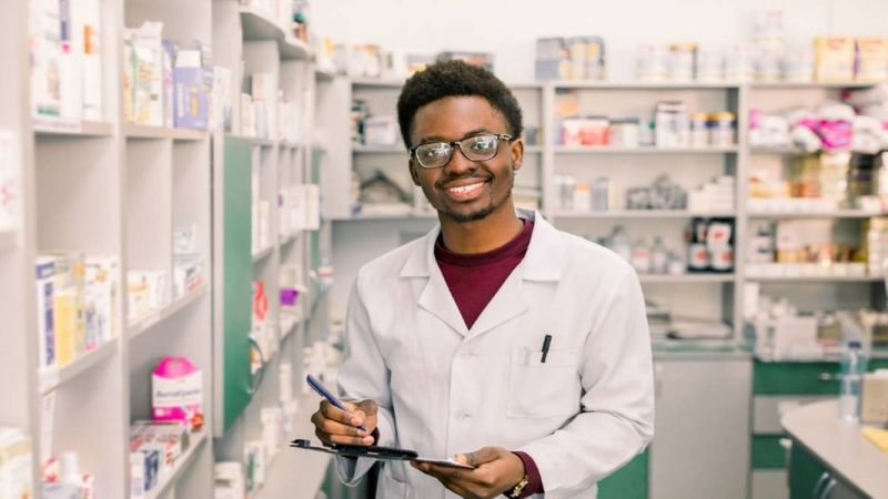 Young pharmacist smiling at work
