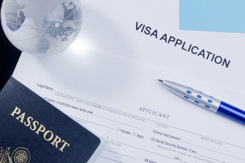 Canadia visa application form with passport and glass globe