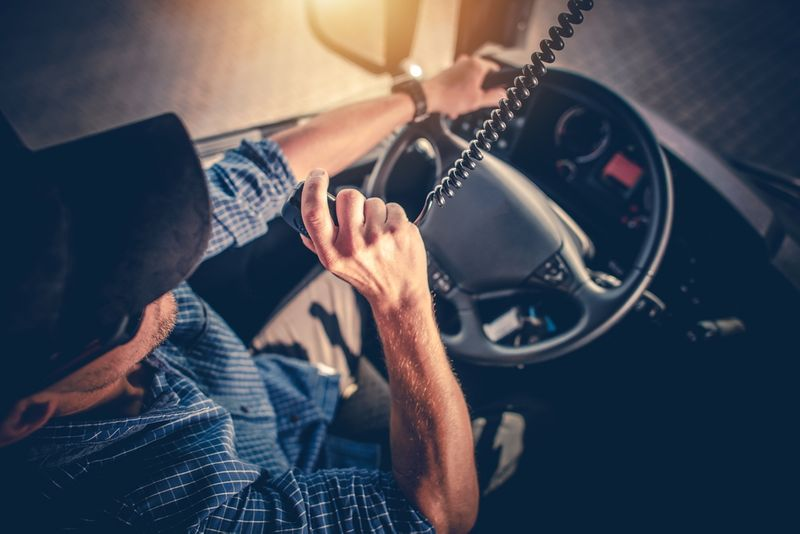 Canadian Truck Driver speaking on CB radio while holding the steering wheel