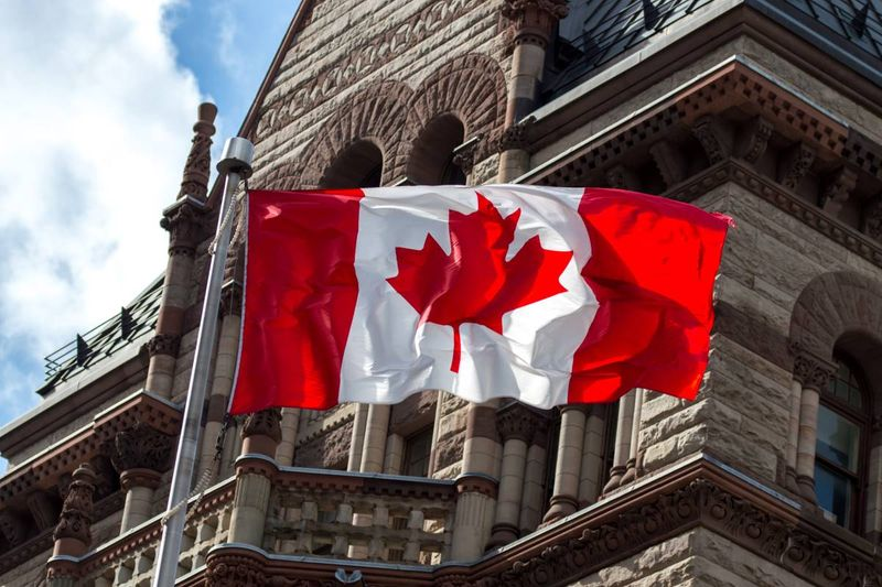 Canadian flag blowing over city immigrate to Canada