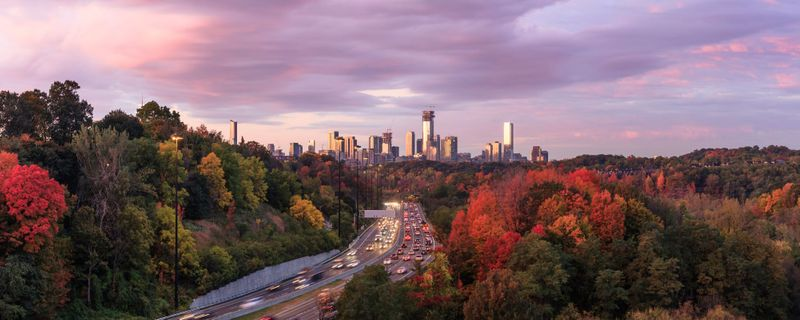Cars approaching downtown Toronto via the Don Valley Parkway in the peak color of autumn at sunrise, Ontario, Canada
