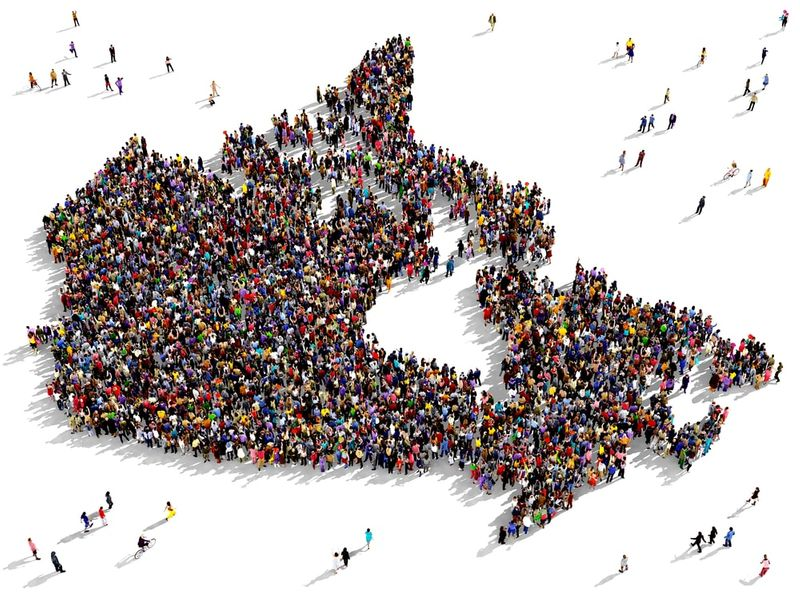 Diverse group of people seen from above gathered together in the shape of Canada | live and work in Canada