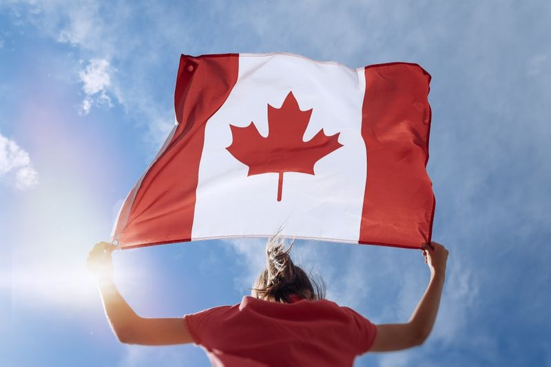 Girl-waving-Canadian flag on top of mountain at sky background
