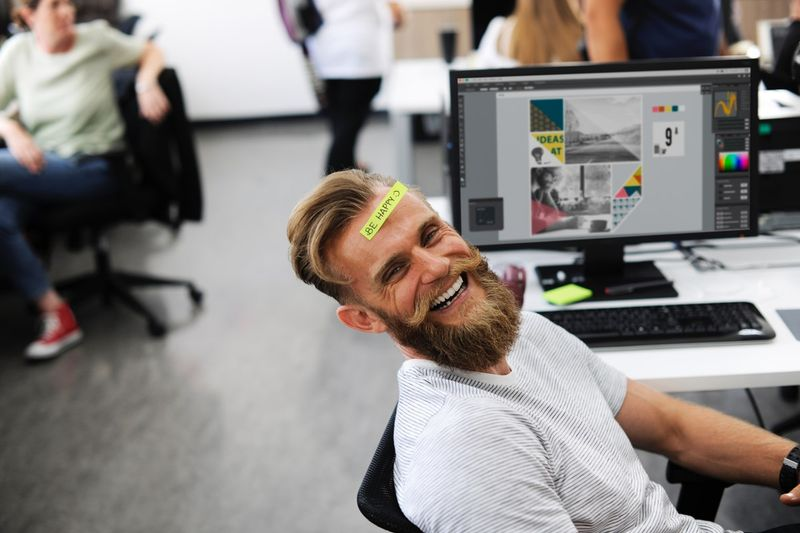 Happy laughing Canadian adult employee at desk with computer