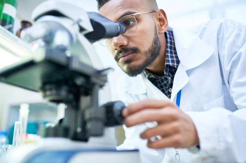 Indian man scientist looking into microscope in lab | business immigration to Canada
