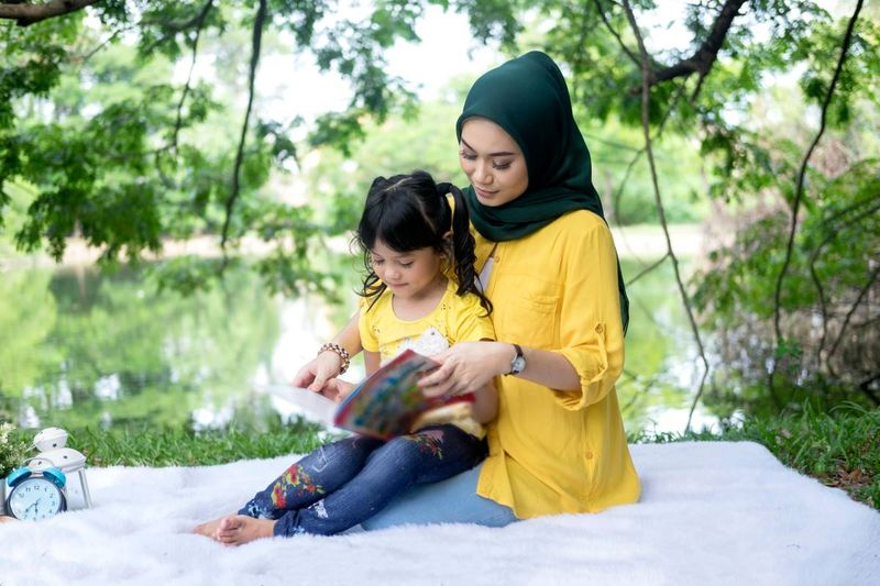 Malaysian woman wearing hijab sitting in park with girl   how to apply for a Canadian visa from Malaysia
