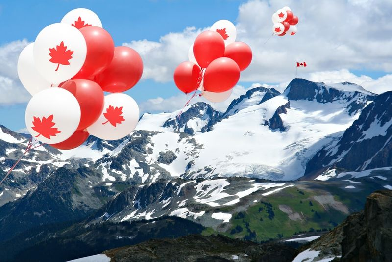 Maple leaf balloons floating over the Rocky mountains with a Canadian flag in the distance Alberta Canada