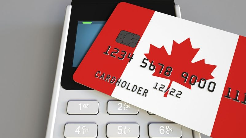 Payment or POS terminal with credit card featuring flag of Canada