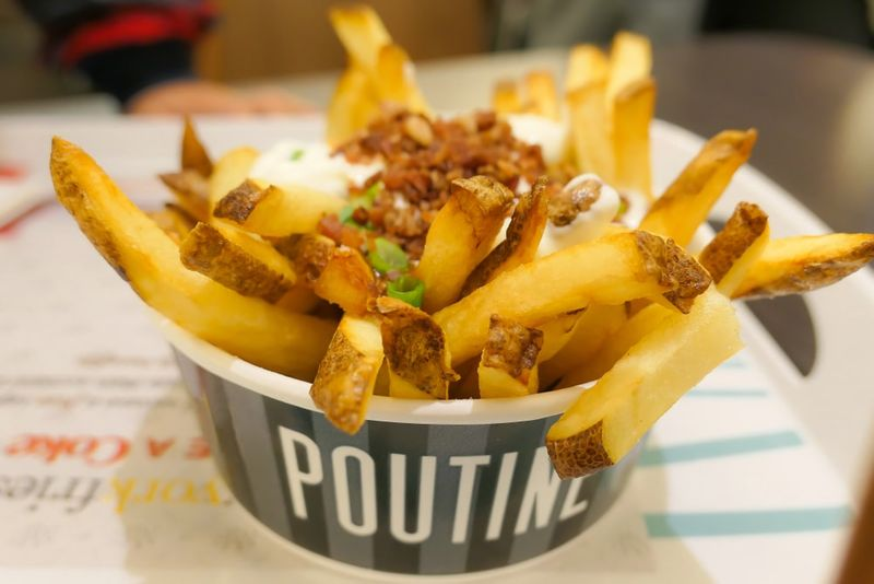 Poutine traditional Canadian meal with fries curd cheese and sauce on the table