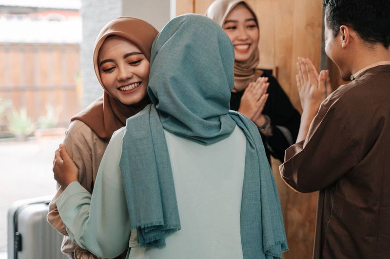 Smiling beautiful Malaysian women wearing hijabs greeting each other   how to apply for a Canadian visa from Malaysia