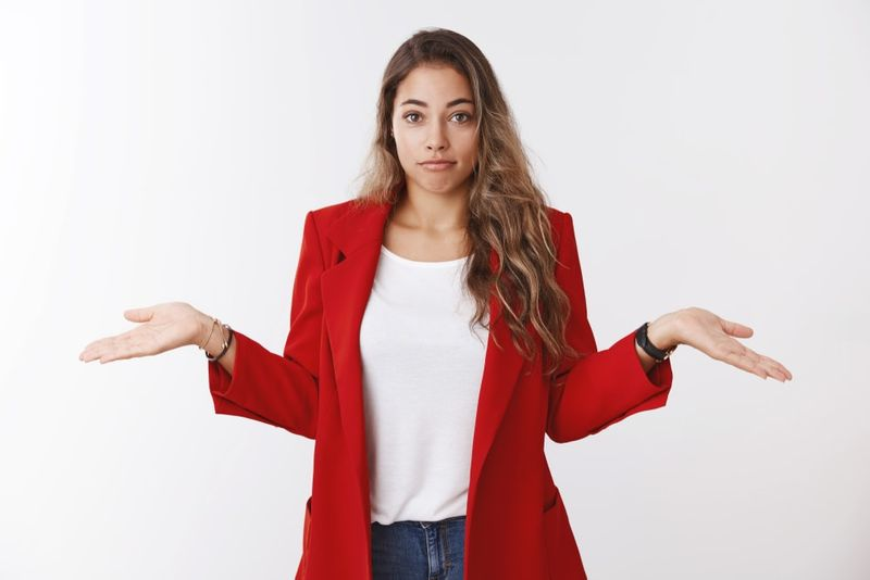 Unsure Canadian caucasian women with long hair wearing a red jacket white tshirt and jeans