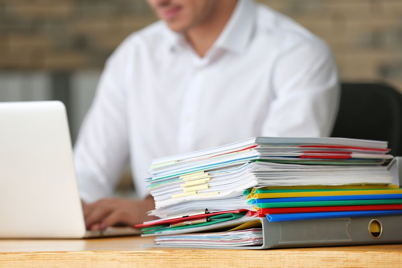 man sitting with stack of files
