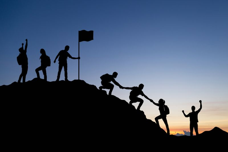people helping each other climb a hill