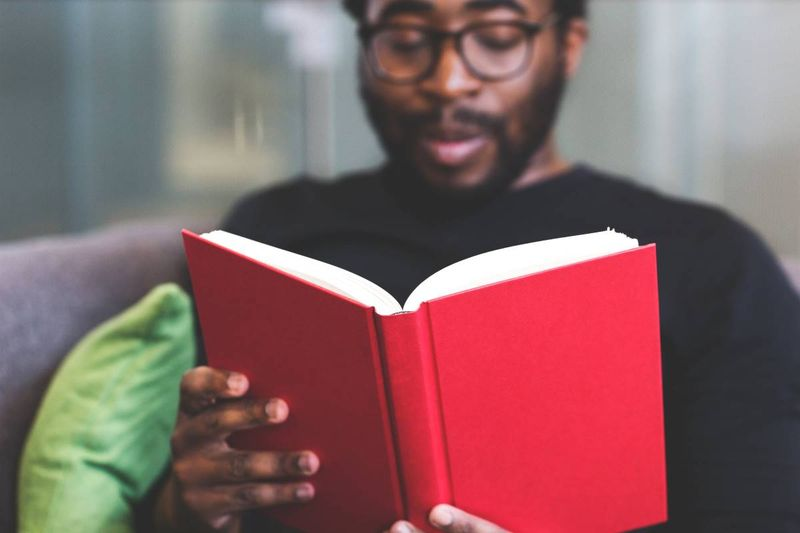 man reading a red book | immigrate to Canada