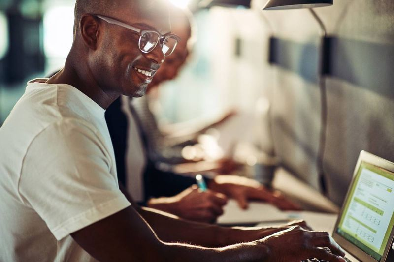 African American man smiling while working on laptop | tech jobs in Canada