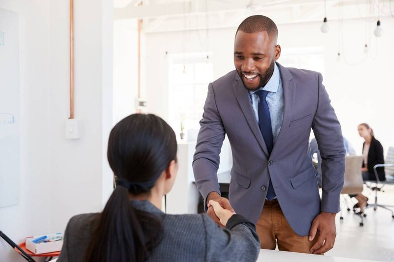 man shaking hands with woman in office |  how to apply for a Canada visa from the DRC
