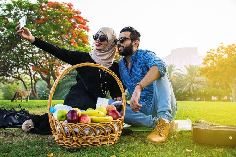 happy Lebanese couple sitting on grass having picnic in park | immigrate to Canada from Lebanon