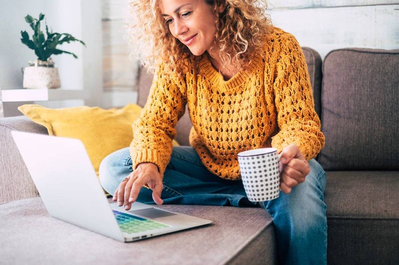 beautiful blonde woman working on laptop | immigrate to Canada