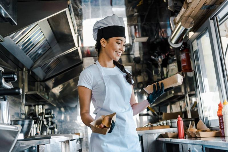 beautiful female chef in food truck serving hotdogs | business immigration to Canada
