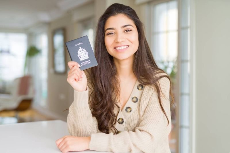 beautiful smiling woman holding Canadian passport | immigrate to Canada in 2020