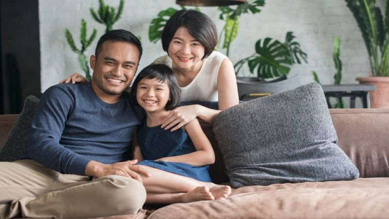 Happy Chinese family posing on couch for camera
