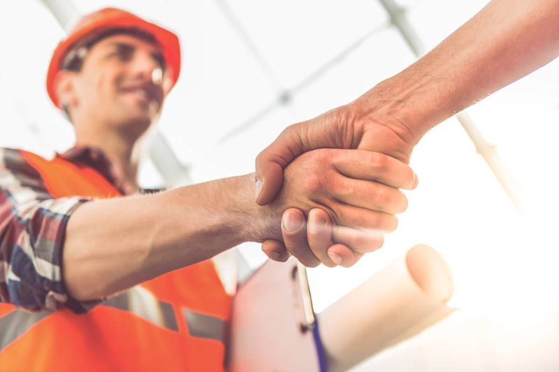 construction worker shaking hands with employer |  immigrate to Canada