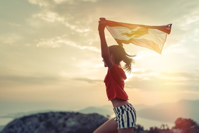 girl holding blowing Canadian flag at sunset