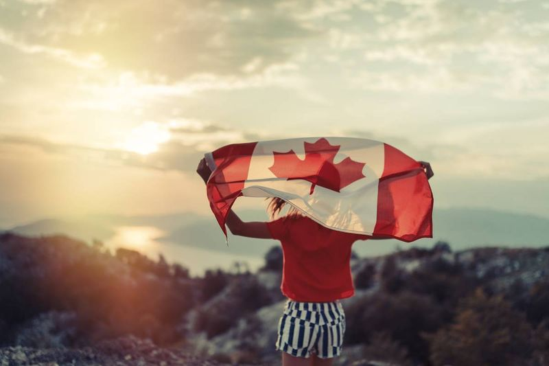 girl holding Canadian flag at sunset | scam or real