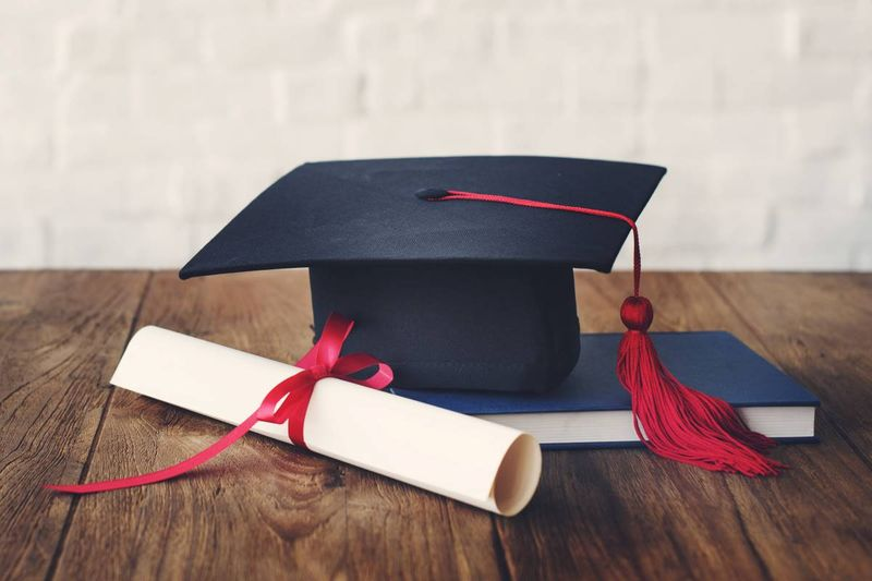 graduation cap, certificate degree and blue book on table | jobs in Canada