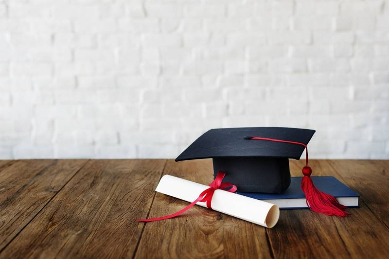 graduate cap with diploma and book on desk  |  13 reasons why you should move to Canada