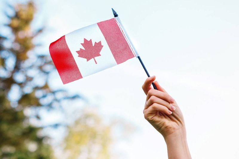 hand holding Canadian flag