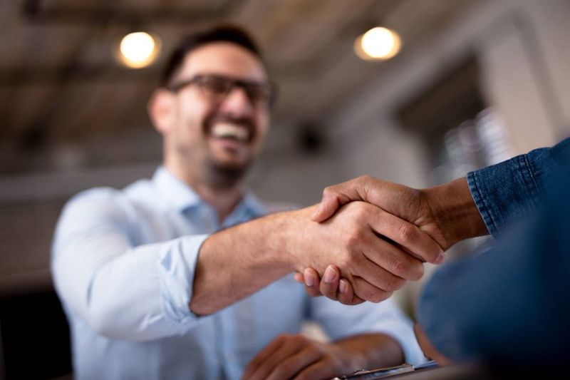 professional handshake after helping person with Canadian visa application | jobs in Canada