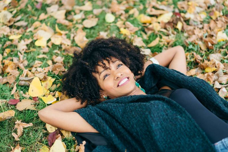 happy african woman lying on grass |  how to apply for a Canada visa from Uganda