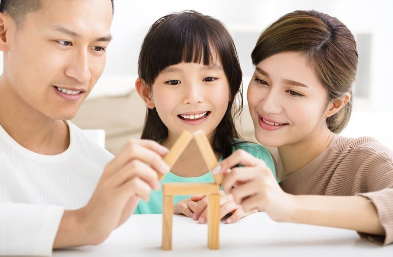 happy asian family playing with toy blocks in Canada