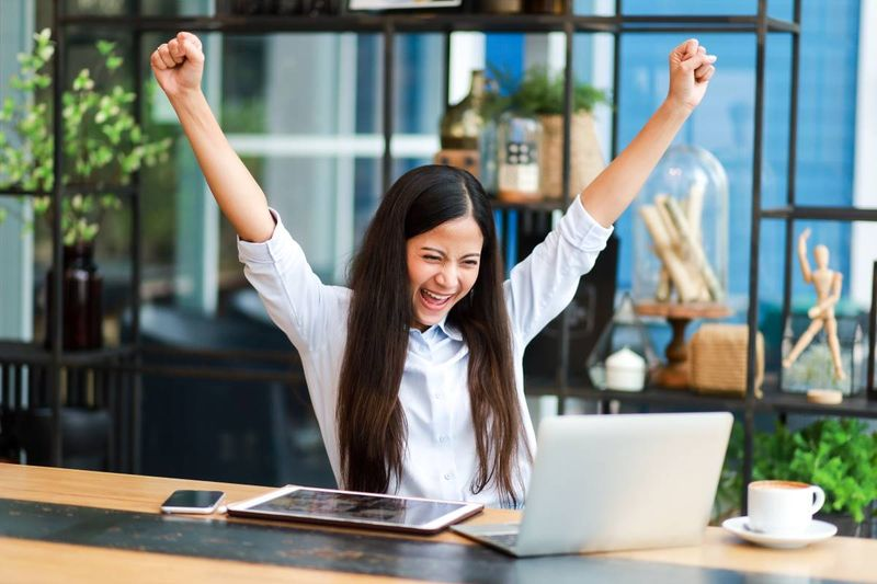 happy Asian woman celebrating after receiving an invitation to apply for permanent residence in Canada