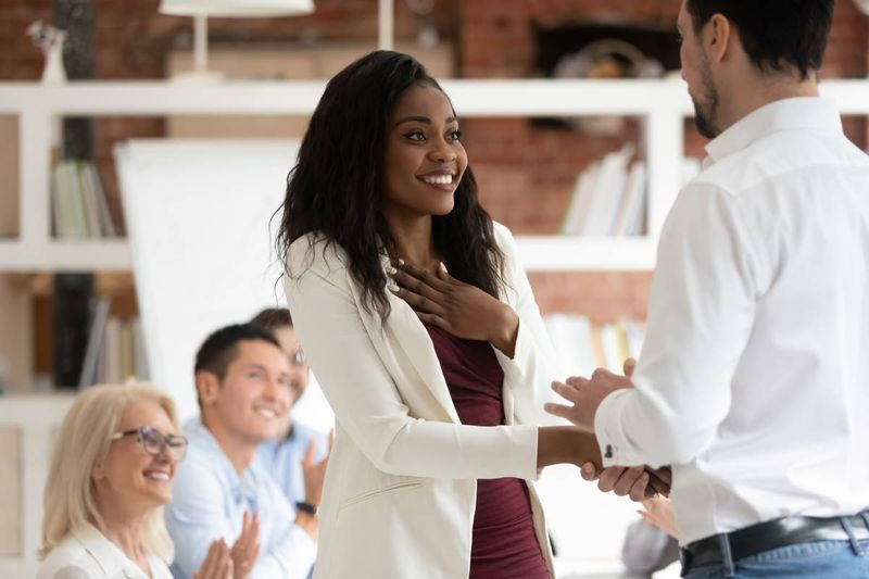 Black female shaking new employer's hand after immigrating to Canada