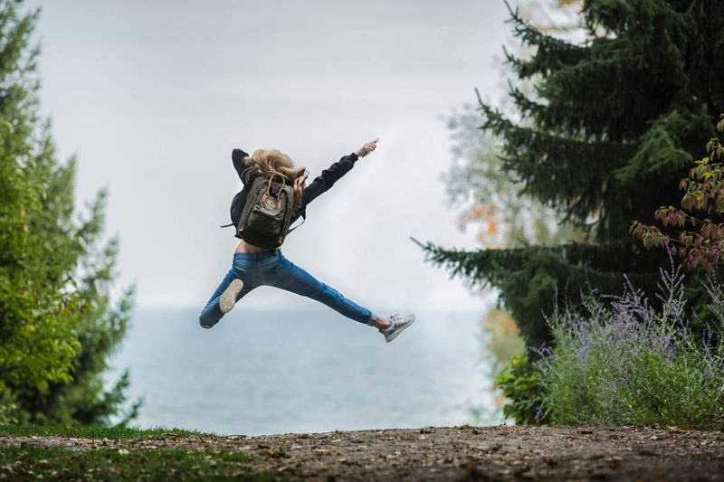 happy blonde jumping with joy after being accepted to study in Canada