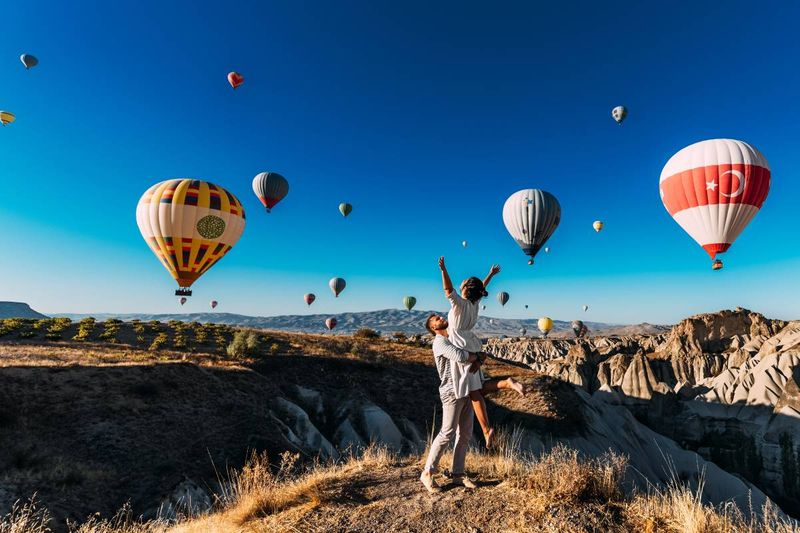happy couple celebrating at festival of balloons Cappadocia Turkey | how to immigrate to Canada