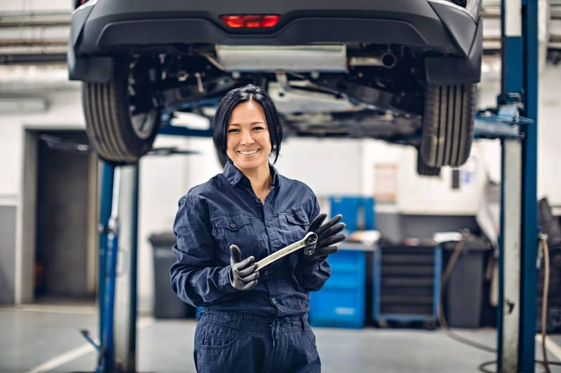happy-female-mechanic-standing-under-car   Canada Express Entry