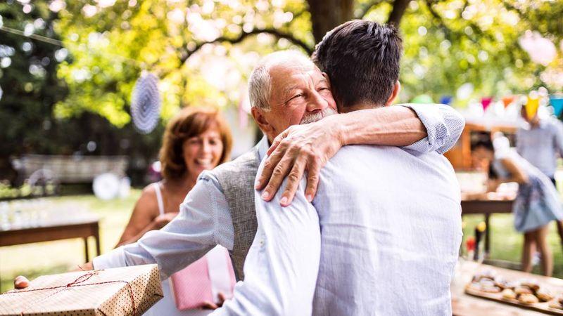 happy-grandparent-hugging-son-at-family-celebration-in-backyard   family sponsorship to Canada