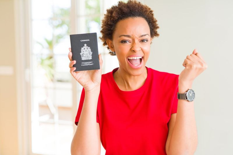 happy international female student wearing red t-shirt holding Canada passport | study in Canada