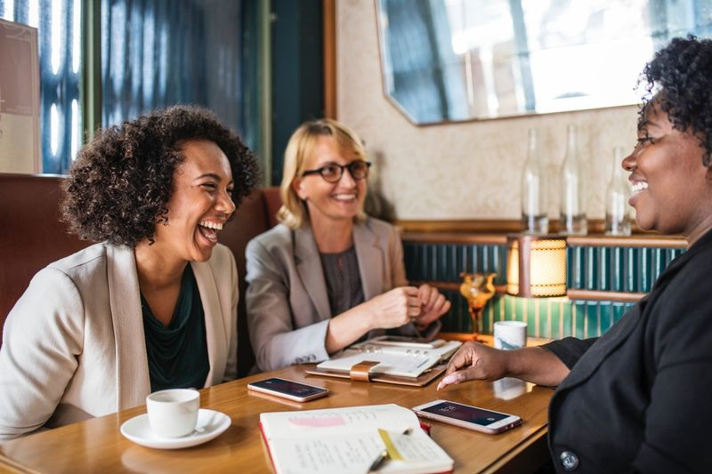 happy laughing female Canadian employees working at table