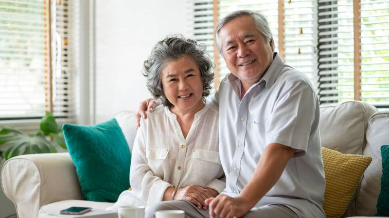 happy smiling Asian grandparents on couch   Parents and Grandparent Sponsorship Program Canada