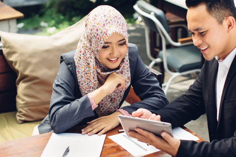 malaysian woman and man looking at ipad at work   how to apply for a Canadian visa from Malaysia