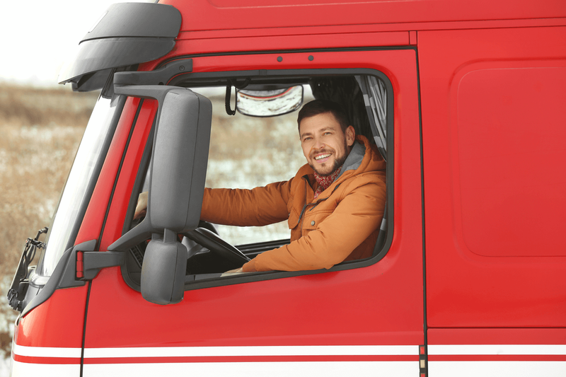 man driving a red truck
