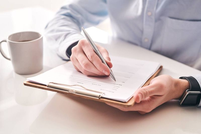 man completing application form on clipboard cup of coffee | jobs in Canada