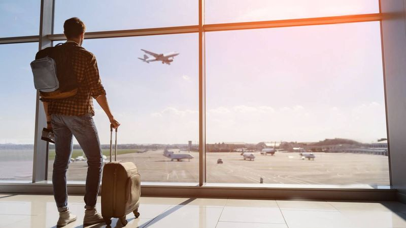 man-standing-at-airport-with-suitcase-and-backpack-watching-plane-take-off | immigrate to Canada