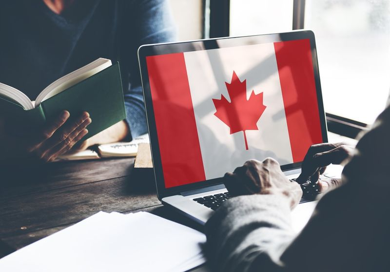 man with laptop with Canadian flag on screen in front of woman with book